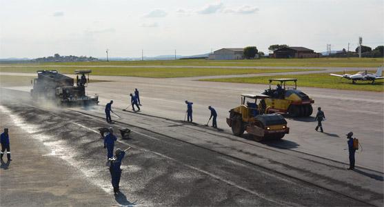 Imagem das obras de recuperação do pavimento do sistema de pista e pátio do Carlos Prates, com funcionários fazendo os trabalhos de recapeamento com máquinas e outros equipamentos.