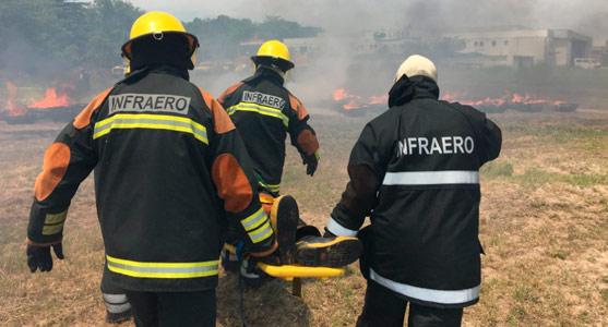 Três bombeiros carregam uma vítima em maca durante exercício prático do Ateba em Jacarepaguá.