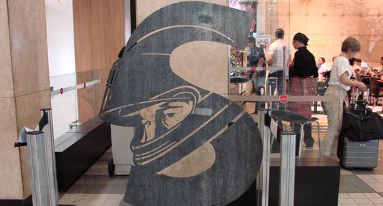"""Foto da obra """"A Concentração, uma escultura em forma de S que reproduz a cabeça do piloto Ayrton Senna com seu capacete de piloto. O trabalho está exposto no saguão de Congonhas."""