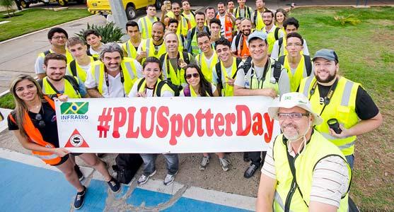 Grupo de spotters que participaram do Spotter Day na Pampulha posam para foto com um banner, onde está escrito #PLUSpotterDay.