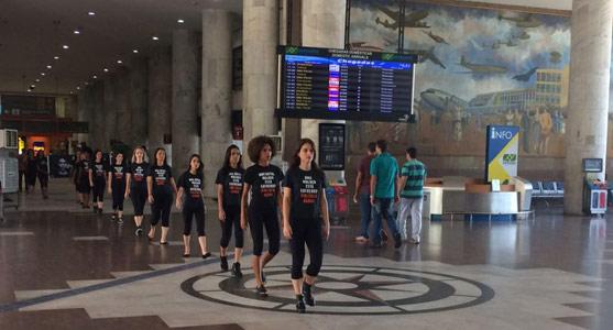 """Modelos da ação da campanha """"A Verdade Dói"""" caminham pelo saguão do Santos Dumont, vestidas com roupas pretas que trazem nas camisetas dados sobre a violência contra a mulher no Brasil."""