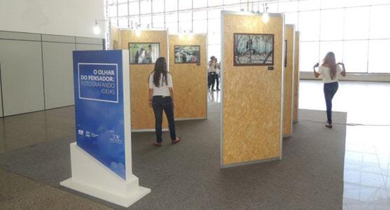 """Foto da exposição """"O Olhar do Pensador: Fotografando Ideias"""" no mirante do Aeroporto de Fortaleza. Na imagem, algumas pessoas observam as fotografias dispostas em murais individuais."""