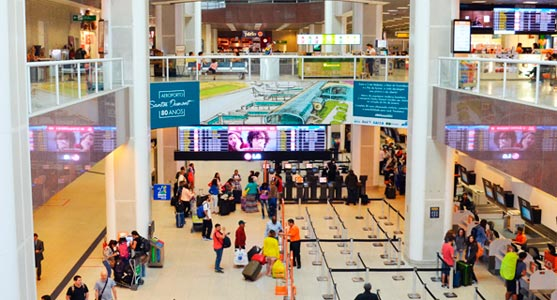Imagem vista de cima do saguão do Santos Dumont, de onde pode se ver o movimento dos passageiros na área de check-in e também um banner comemorativo dos 80 anos do aeroporto, que traz um desenho estilizado do terminal de passageiros.