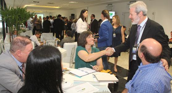 Foto de empresários e gestores da Infraero se cumprimentando e conversando sobre negócios durante intervalo na cerimônia de apresentação do Voo de Negócios de Curitiba.