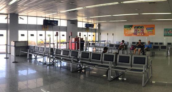 Imagem da sala de embarque do Aeroporto de Aracaju, em frente a dois dos portões de embarque, com longarinas organizadas e passageiros sentados à espera de seus voos.