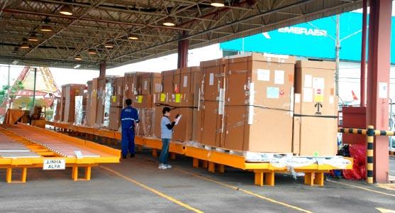 Processo de movimentação de volumes no terminal de logística de carga de São José dos Campos. Na imagem, um funcionário faz anotações em uma planilha enquanto outro monitora as cargas distribuídas em paleteiras.