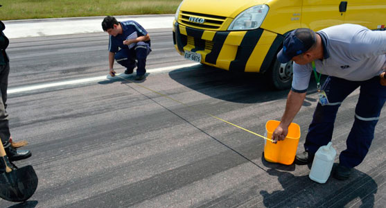 Funcionários da Infraero fazem, com uma trema, a medição de diâmetro em uma área de pista.