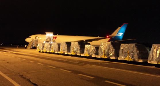Imagem de volumes de carga no Aeroporto de Belém sendo levados para um avião da TAM Cargo em uma operação noturna.