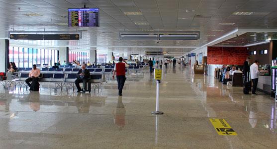 Imagem interna da sala de embarque do Aeroporto de Curitiba, com passageiros transitando, sentados ou fazendo compras.