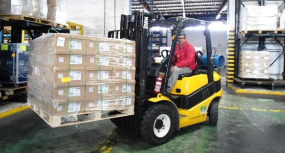 Um funcionário com empilhadeira move volumes de cargas no terminal logístico do Aeroporto de Porto Alegre.