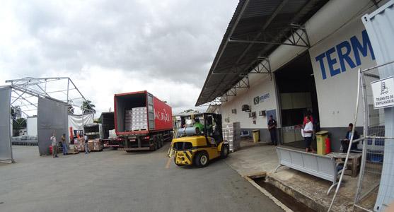 Caminhão e empilhadeira se preparando para descarregar volumes na entrada do terminal de importação do Teca de Goiânia.