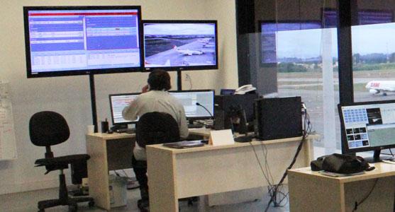 Foto do interior do novo CGA do Aeroporto de Curitiba, com alguém trabalhando diante de monitores que registram estatísticas e imagens das operações do terminal.