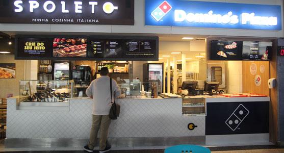 78ad384c38a Imagem de um cliente no balcão das lojas Spoleto e Domino s recentemente  inauguradas no Aeroporto do