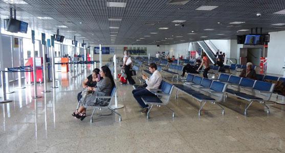 Imagem da sala de embarque do Aeroporto de Cuiabá, com passageiros aguardando seus voos sentados em longarinas.